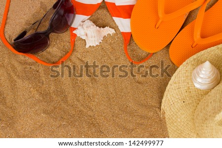 orange sandals  and sunbathing accessories at sand with copy space
