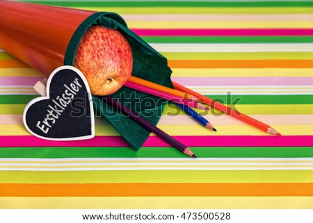 orange school cone with money, concept and german text for school beginner