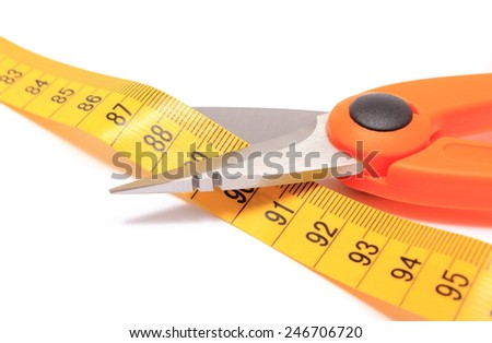 Orange scissors cutting tape measure on white background, concept for slimming - stock photo