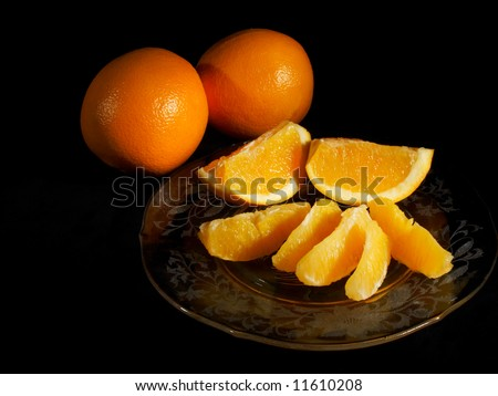 Orange sections on a glass plate with two whole oranges, light painted on black
