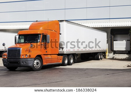 Orange semi truck by the door of warehouse - stock photo