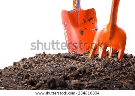 Orange shovels dig in soil isolated on white background - stock photo