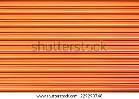 Orange shutter roller steel door texture background. - stock photo