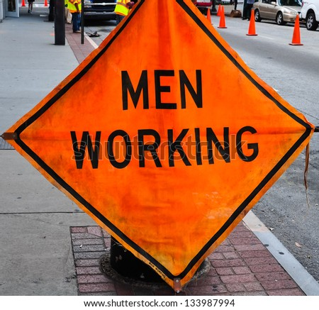 orange sign indicating men working in a street scene - stock photo