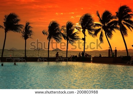 orange sky when sunset in the horizon with the swimming pool - stock photo