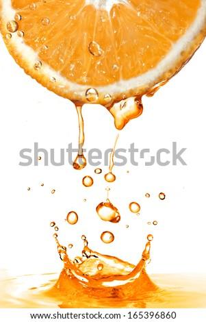 orange slice and splash of juice isolated on white - stock photo