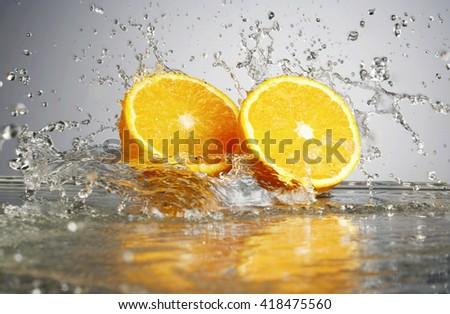 Orange slice in water splash, isolated - stock photo
