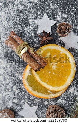 orange slices and cinnamon ticks on a slate covered by flour