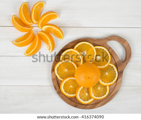 Orange slices are well decorated on a cutting board. Top view composition. Food decoration. Boosting immune system. Helps prevent ageing of skin. Protects your vision. - stock photo