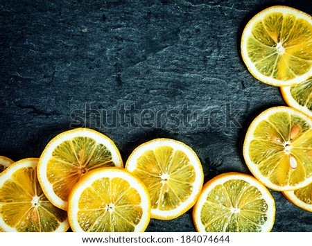 Orange slices arranged in a corner decoration on a dark grey textured slate background with copyspace for your text - stock photo