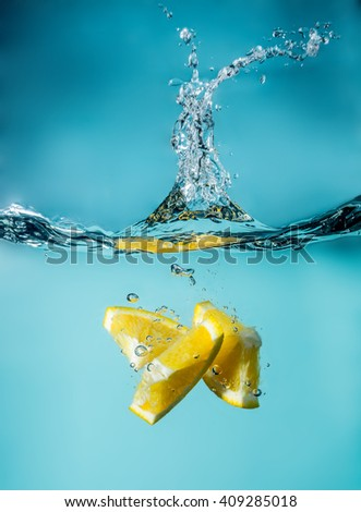 Orange slices falling into the blue water close-up, macro, splash water, bubbles,  light blue celestial sky background - stock photo