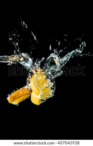 Orange slices falling into the water close-up, macro, splash water, bubbles, isolated, black background - stock photo
