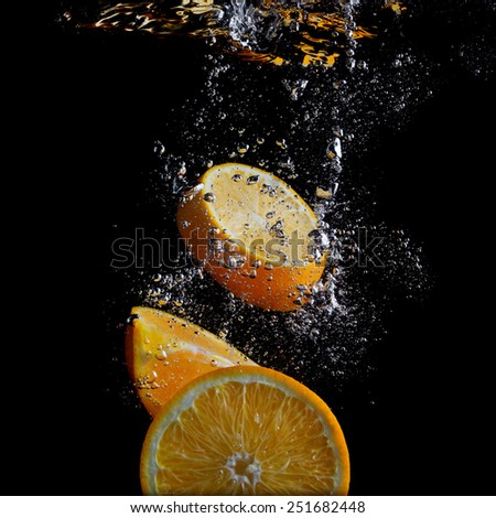 Orange slices falling into the water. Photo on black background. - stock photo