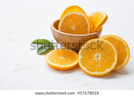 Orange slices in bowl on white rustic wooden table, summer and healthy concept