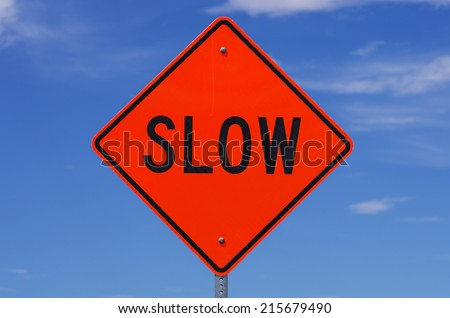 orange slow road sign with black letters in front of the sky - stock photo