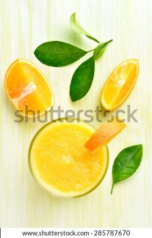 Orange smoothie in glass, top view - stock photo
