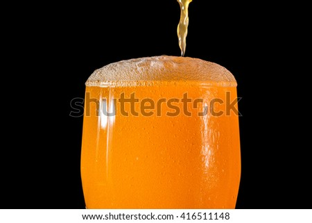 Orange soda large glass, overflowing glass of orange soda closeup with bubbles isolated on black background - stock photo