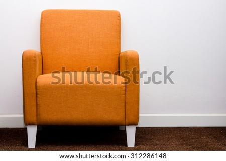 Orange sofa furniture on white wall background - stock photo