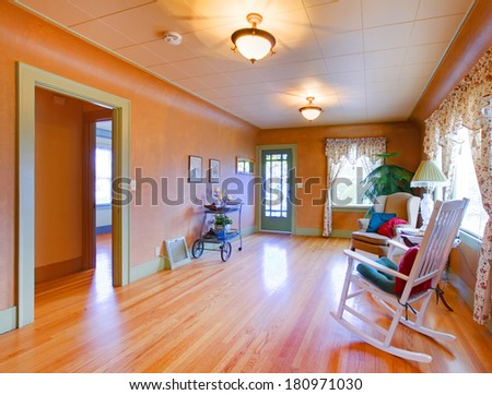 Orange spacious living room with antique cart, rocking chair
