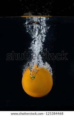 Orange splash on black background - stock photo