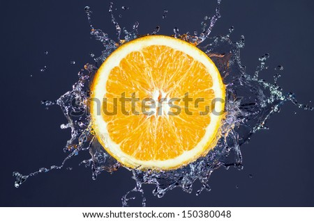 orange splash with water before blue background - stock photo