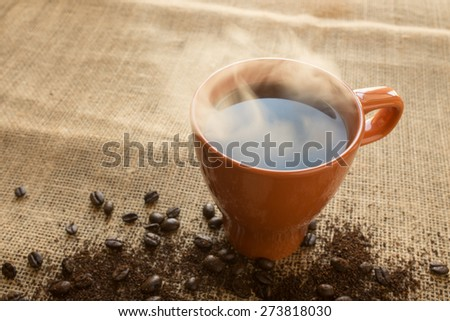 Orange steaming coffee cup - stock photo