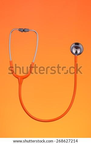 Orange stethoscope isolated on orange background - stock photo