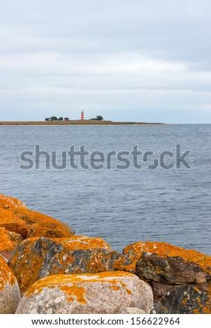 Orange stones on the coastline of Gotland, Sweden. Lighthouse on the other shore. - stock photo