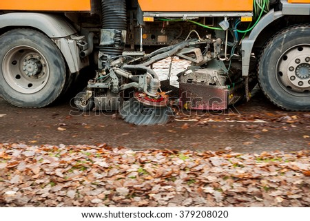 Orange street sweeper machine cleaning the street after in fall from fallen foliage - stock photo