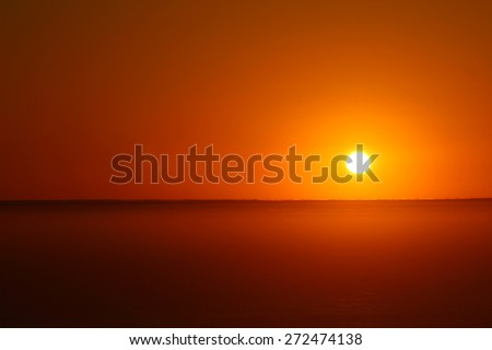 Orange sun setting over fog bank - stock photo