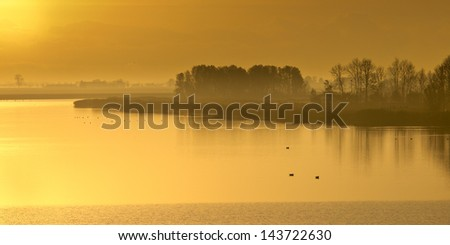 Orange sunrise over a Broad River in National Park Lauwersmeergebied , the Netherlands - stock photo