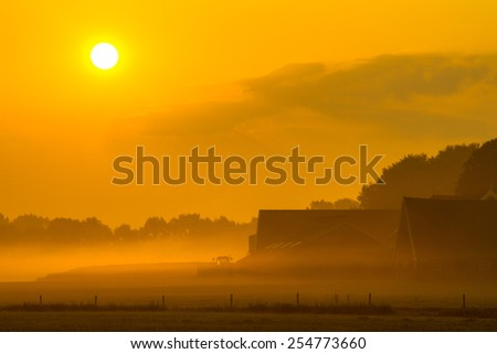 Orange sunrise over misty farm with barns and tractor in Twente, Netherlands