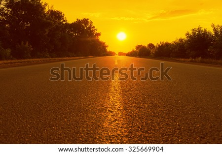 orange sunset and asphalt road. soft focus - stock photo