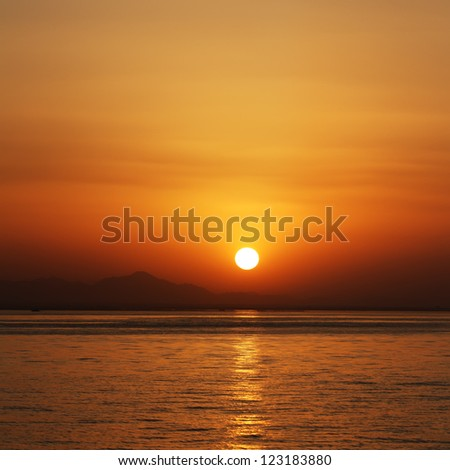 orange sunset at the sea with mountains silhouettes - stock photo