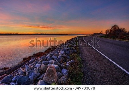 Orange sunset by the side of the road and placid river - stock photo