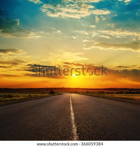 orange sunset in clouds over asphalt road - stock photo