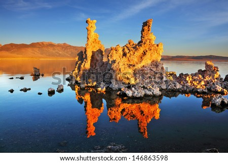 Orange sunset on Mono Lake. Outliers - bizarre calcareous tufa formation reflected in the smooth water. - stock photo