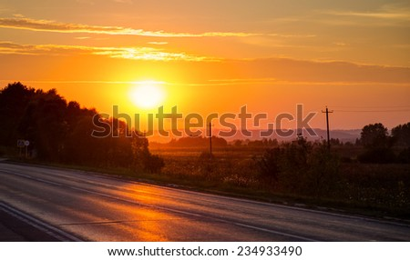 Orange sunset over asphalt road. Horisontal photo - stock photo