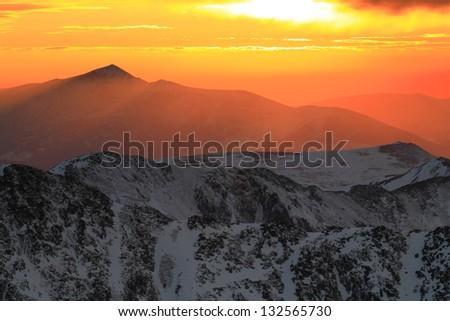 Orange sunset over the snowy mountains - stock photo