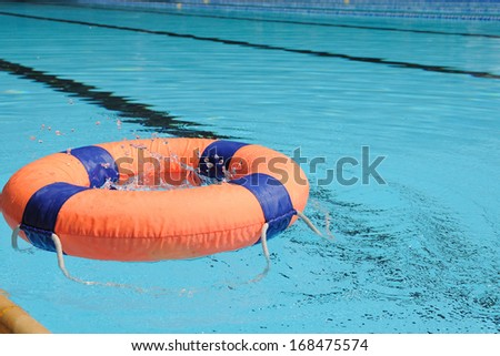 Orange swim ring with deep blue trim floating on water, water action. - stock photo