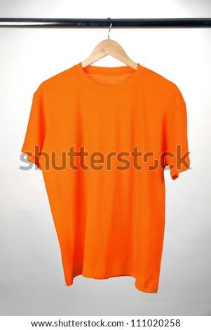 Orange t-shirt on hanger on white background - stock photo