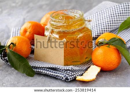 orange (tangerine) jam in a glass jar on the table - stock photo