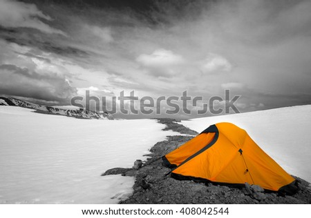 Orange tent in snow mountains. Turkey, Central Taurus Mountains, Aladaglar (Anti-Taurus), plateau Edigel (Yedi Goller). Selective color. - stock photo