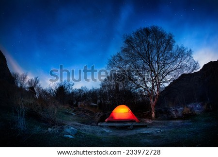 Orange tent in the mountain valley at blue night sky with stars in Kazakhstan - stock photo