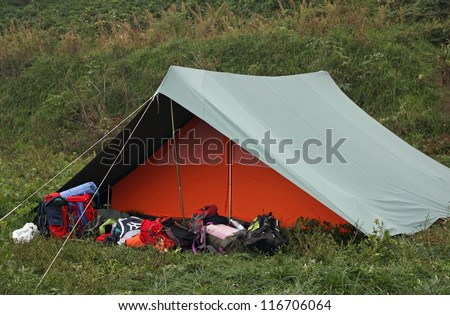 Orange tent with many backpacks deposited in front of the entrance - stock photo