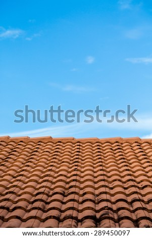 Orange tile roof under blue sky with soot from chimney