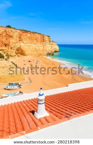 Orange tiles on roof of a house on sandy Benagil beach in Algarve region of Portugal - stock photo