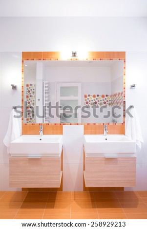 Orange tiles on the floor in modern toilet