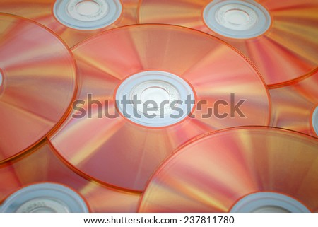 Orange tinted close-up of a stack of cd-roms - stock photo