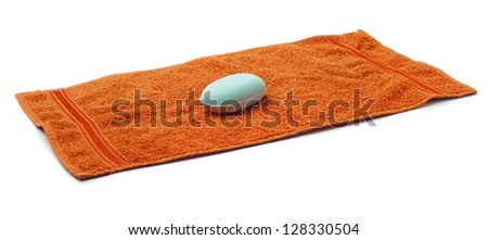 Orange Towel with bar of blue Soap. - stock photo